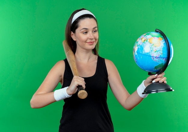 Young fitness woman in headband holding baseball bat and globe looking at it with smile on face standing over green background
