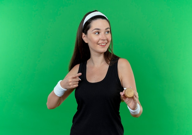 Young fitness woman in headband holding baseball bat looking aside smiling with happy face pointing with finger to the side standing over green wall
