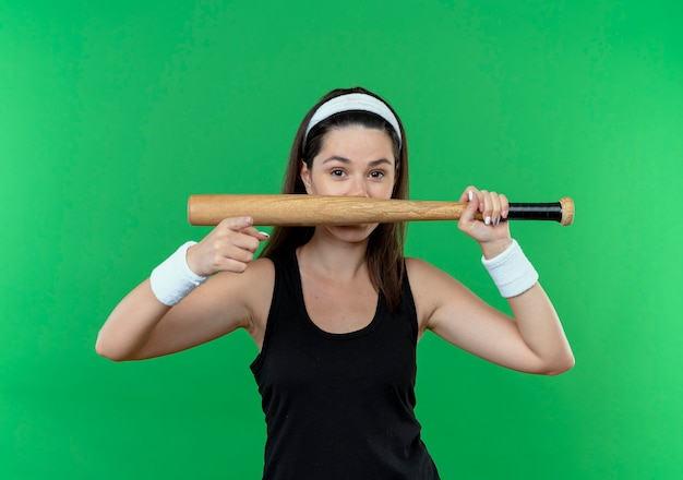 Young fitness woman in headband holding baseball bat  pointing with finger  smiling standing over green wall
