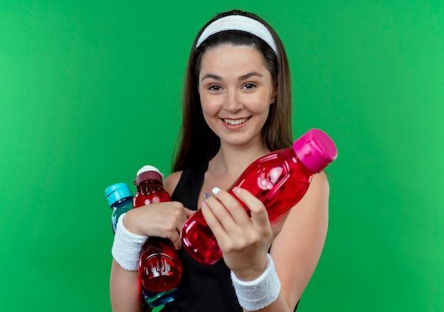 Giovane donna fitness in fascia tenendo le bottiglie di acqua che offre uno di loro sorridente guardando la fotocamera in piedi su sfondo verde
