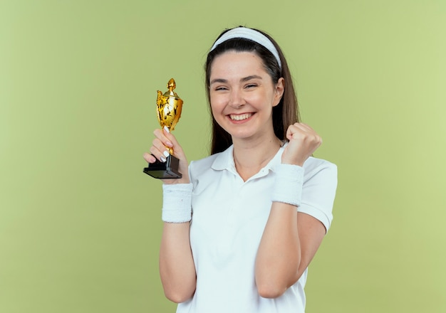Young fitness woman in headband holding her trophy happy and excited clenching fist standing over light wall