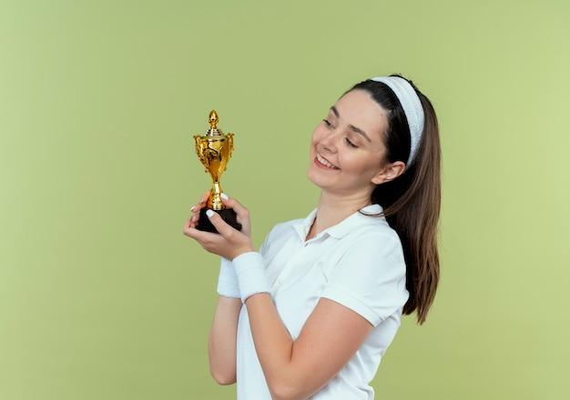 Giovane donna fitness in fascia tenendo il suo trofeo guardandolo sorridendo con la faccia felice in piedi sopra il muro di luce
