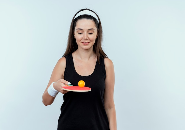 Young fitness woman in headband holding racket and ball for table tennis smiling confident standing over white background