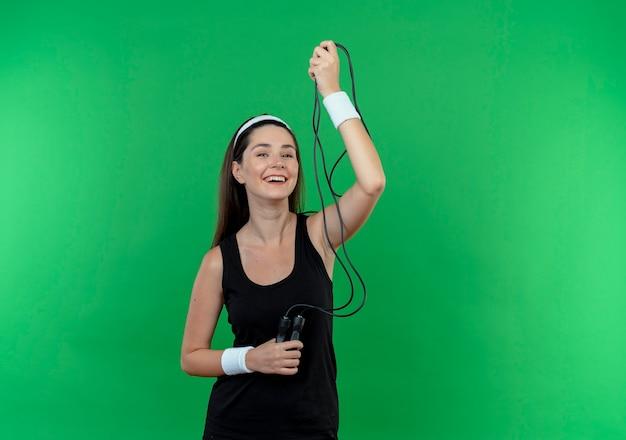 Giovane donna fitness in fascia tenendo la corda per saltare sorridendo allegramente in piedi sopra la parete verde