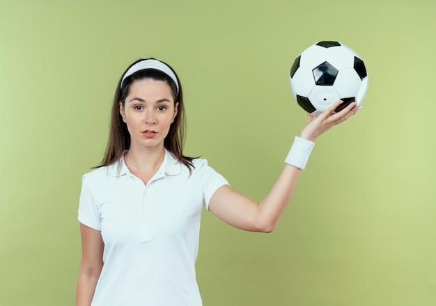 Giovane donna fitness in fascia tenendo il pallone da calcio con la faccia seria in piedi sopra il muro di luce