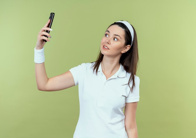 Giovane donna fitness in fascia cercando confuso tenendo selfie utilizzando lo smartphone in piedi sopra la parete leggera