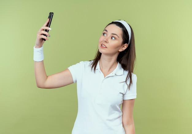 Giovane donna fitness in archetto cercando confuso tenendo selfie utilizza lo smartphone in piedi sopra la parete leggera