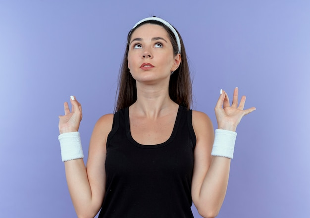 Young fitness woman in headband looking up making meditation gesture with fingers standing over blue background