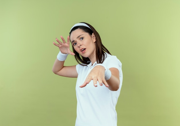 Giovane donna fitness in fascia che fa il gesto di difesa con le mani che guarda l'obbiettivo con espressione di paura in piedi su sfondo chiaro