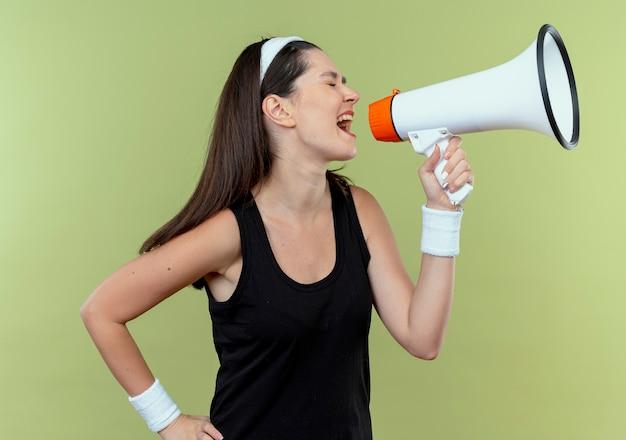 Giovane donna fitness in fascia che grida al megafono con espressione aggressiva in piedi sopra il muro di luce