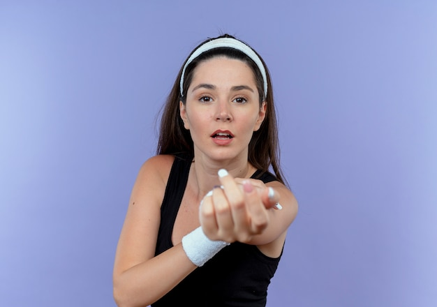 Giovane donna fitness in fascia che allunga le mani che guarda l'obbiettivo con espressione fiduciosa in piedi su sfondo blu