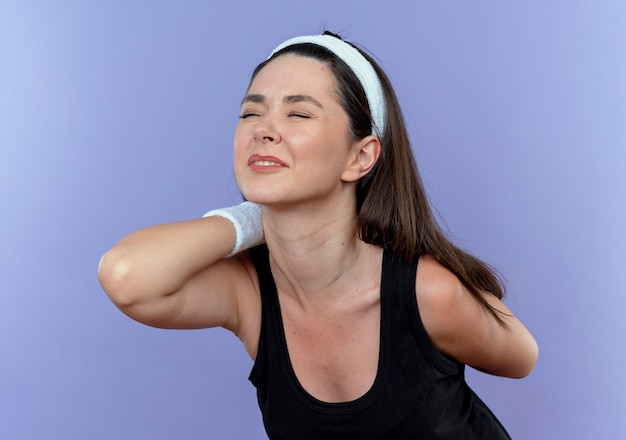 Young fitness woman in headband touching her back feeling pain standing over blue wall