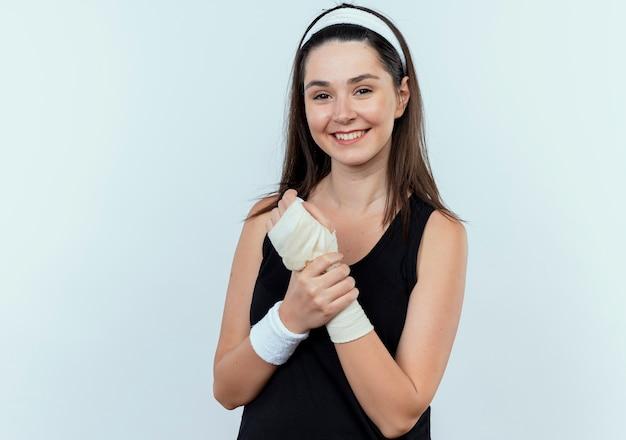 Giovane donna fitness in fascia toccando il suo polso fasciato guardando la fotocamera con il sorriso sul viso in piedi su sfondo bianco