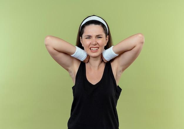 Giovane donna fitness in fascia che tocca il suo collo alla ricerca di malessere sensazione di dolore in piedi su sfondo chiaro