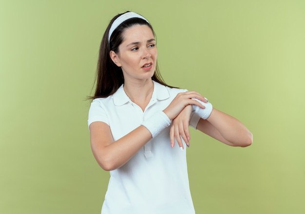 Giovane donna fitness in fascia che tocca il suo polso cercando dispiaciuto sensazione di dolore in piedi sopra la parete leggera