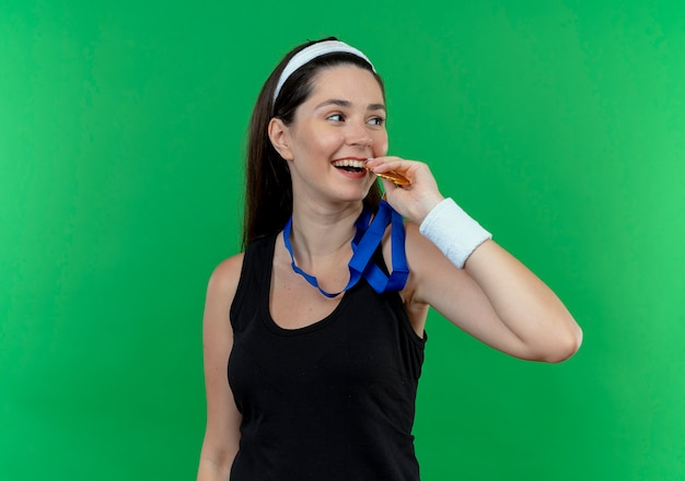 Young fitness woman in headband with gold medal around her neck biting it smiling cheerfully standing over green background