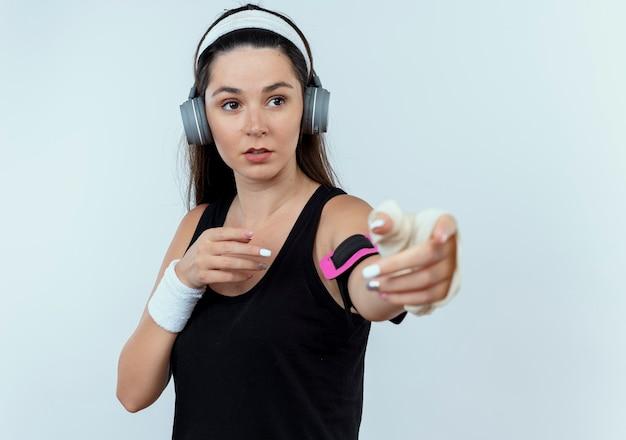 Giovane donna fitness in archetto con cuffie e fascia da braccio dello smartphone che osserva da parte con le braccia fuori in piedi su sfondo bianco