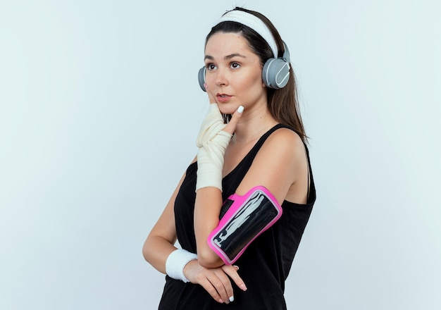 Giovane donna fitness in archetto con cuffie e fascia da braccio dello smartphone che guarda da parte con espressione pensierosa con la mano sul mento pensando in piedi sopra il muro bianco