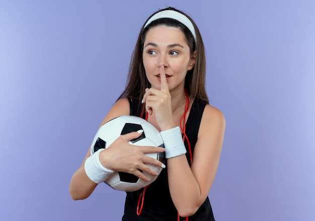 Young fitness woman in headband with skipping rope around neck holding soccer ball making silence gesture with finger on lips standing over blue wall