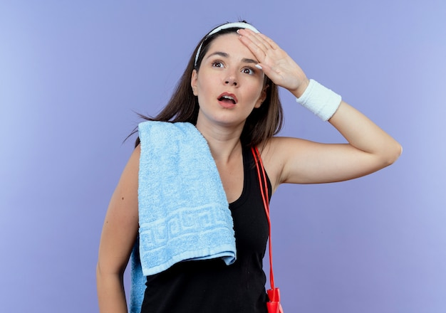 Giovane donna fitness in fascia con un asciugamano sulla spalla guardando da parte sorpreso con la mano sopra la testa in piedi sul muro blu