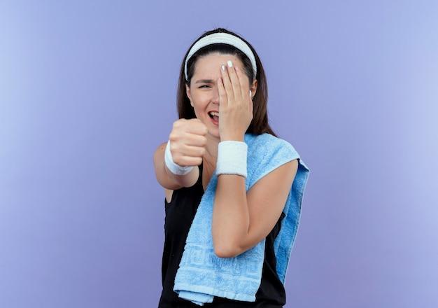 Giovane donna fitness in fascia con asciugamano sulla sua spalla guardando la telecamera che copre un occhio con una mano stringendo il pugno in piedi su sfondo blu