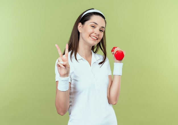 Young fitness woman in headband working out with dumbbell looking at camera smiling showing victory sign standing over light background