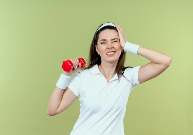 Young fitness woman in headband working out with dumbbell looking confused standing over light wall