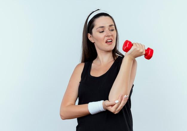 Giovane donna di forma fisica nella fascia che risolve con il dumbbell che sembra teso in piedi su sfondo bianco