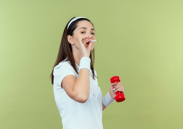 Young fitness woman in headband working out with dumbbell and smoking a cigarette standing over light wall