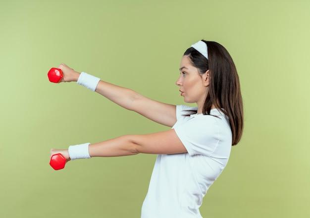 Giovane donna fitness in fascia lavorando con manubri guardando fiducioso in piedi su sfondo chiaro