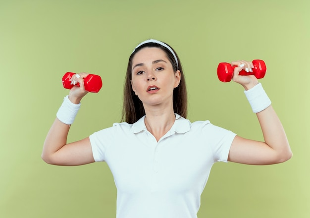 Young fitness woman in headband working out with dumbbells looking confident standing over light wall