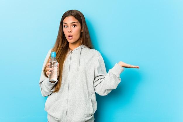Молодая женщина фитнеса, держащая бутылку с водой, впечатлена удерживанием копией пространства на ладони.