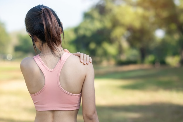 Young fitness woman holding her sports injury shoulder, muscle painful during training. asian runner female having body problem after exercise outside in summer