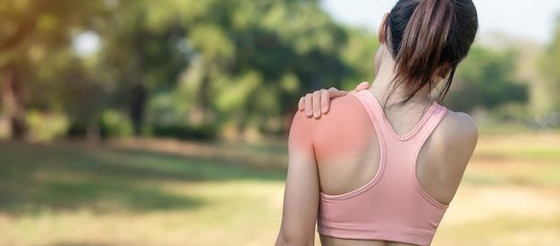 Молодая женщина фитнеса держа ее плечо спортивной травмы, мышцу болезненную во время тренировки.