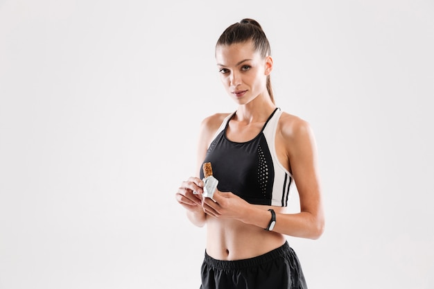 Young fitness woman holding muesli bar and looking