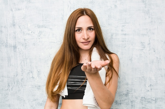 Young fitness woman holding something with palms, offering to camera.