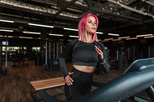 Молодая женщина фитнеса в черной модной спортивной одежде работает на беговой дорожке в тренажерном зале