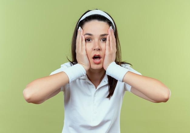 Молодая фитнес-женщина в повязке на голову в шоке, стоя над светлой стеной