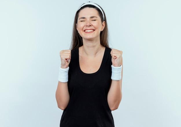 白い背景の上に立って幸せで興奮した拳を食いしばってヘッドバンドの若いフィットネス女性