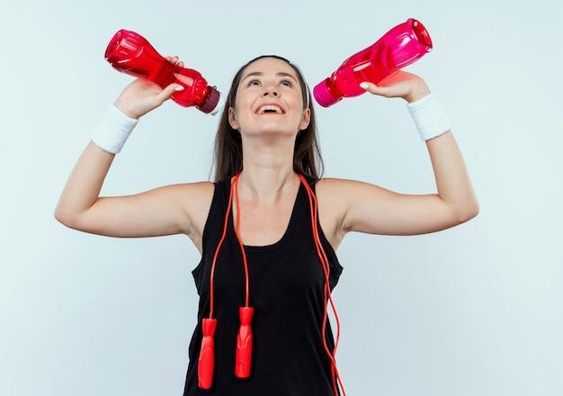 白い壁の上に立っているトレーニングの後にドリングに行く水のボトルを保持しているヘッドバンドの若いフィットネス女性