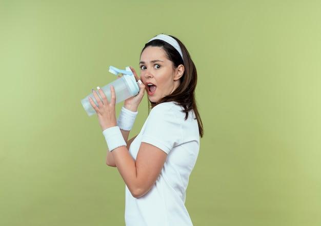 水のボトルを保持しているヘッドバンドの若いフィットネス女性は、光の壁の上に立って驚いた