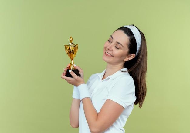 Молодая женщина фитнеса в повязке на голову, держа свой трофей, глядя на него, улыбаясь со счастливым лицом, стоящим над светлой стеной