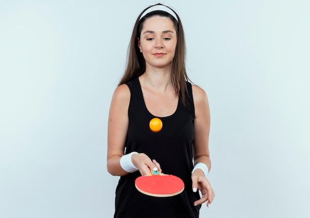 白い壁の上に立って自信を持って笑顔のボールを投げる卓球のためのラケットとボールを保持しているヘッドバンドの若いフィットネス女性