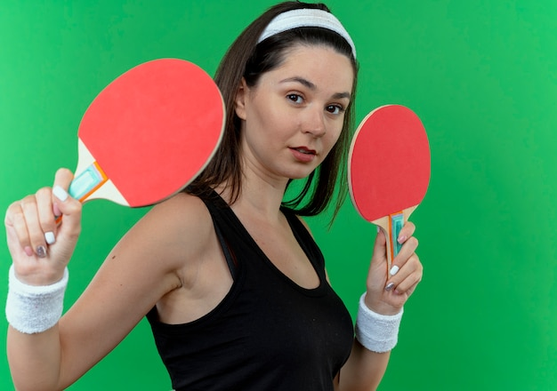 緑の壁の上に立っている自信を持って表情とテニステーブルのラケットを保持しているヘッドバンドの若いフィットネス女性