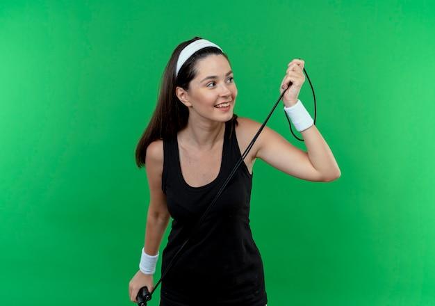 緑の背景の上に立って前向きで幸せな笑顔を脇に見て縄跳びを保持しているヘッドバンドの若いフィットネス女性