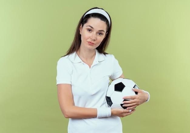 明るい背景の上に立っている自信を持って表情でカメラを見てサッカーボールを保持しているヘッドバンドの若いフィットネス女性