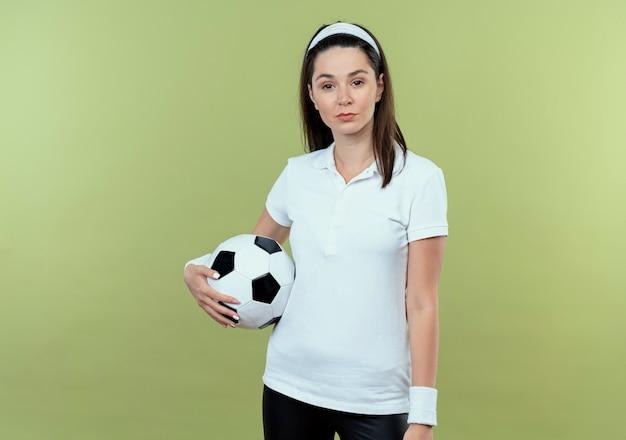 明るい背景の上に立っている真剣な自信を持って表情でカメラを見てサッカーボールを保持しているヘッドバンドの若いフィットネス女性