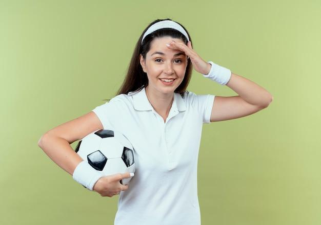 明るい壁の上に立っている間違いのために頭上に混乱して混乱しているサッカーボールを保持しているヘッドバンドの若いフィットネス女性