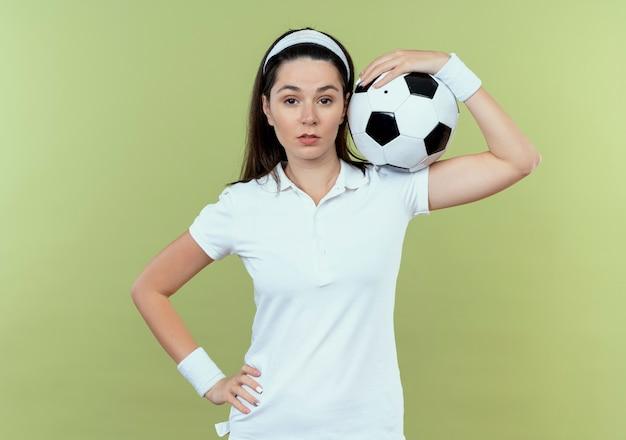 明るい背景の上に立っている自信を持って表情でカメラを見て彼女の肩にサッカーボールを保持しているヘッドバンドの若いフィットネス女性
