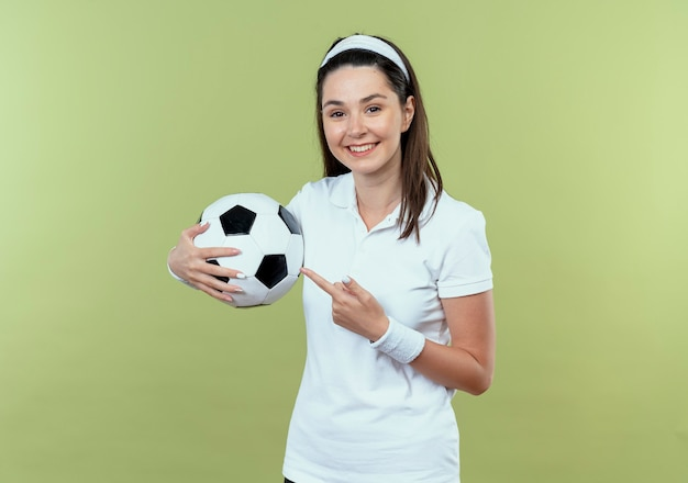 Молодая фитнес-женщина в повязке на голову держит футбольный мяч, указывая пальцем на него, весело улыбаясь, стоя над светлой стеной